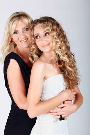'evening wear': beautiful real couple mother in her 40s and teenage daughter wearing evening wear and make-up in studio