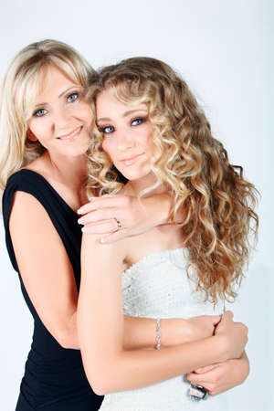 beautiful real couple mother in her 40s and teenage daughter wearing evening wear and make-up in studio photo