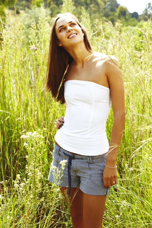 happy beautiful young teenage woman with long brunette hair standing in in shorts in tall grass in the field photo