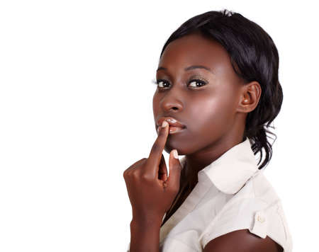 quiet adult: young African American businesswoman wearing light shirt looking with finger on her lips isolated on white with copy cpace Stock Photo