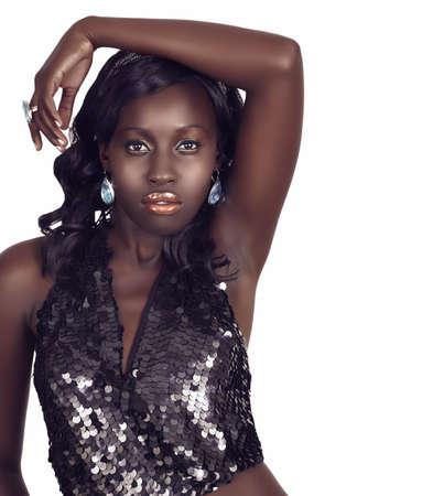 aretes: hermosa mujer afroamericana con maquillaje de moda oro brillante y pelo largo rizado vistiendo top sequin met�lico con espacio de copia en blanco. Foto de archivo