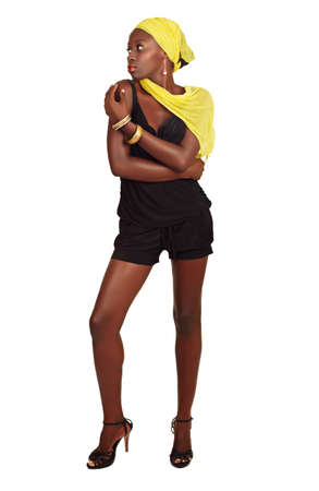 beautiful African model with fit slim body and long legs wearing shorts and yellow head scarf on white background photo