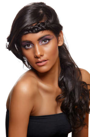 beautiful woman with dark tanned skin and long curly black hair with braid wearing purple artistic make-up with long eyelashes.