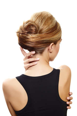 beautiful woman with blond hair in french roll wearing little black dress touching her neck view from the back on white