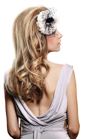 beautiful bride with long blond hair in big hairstyle, wearing flower headband with veil over her face and an open back gray dress on white background.