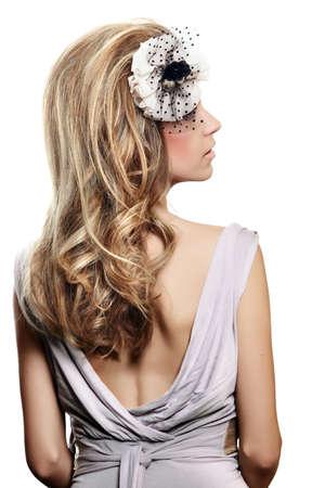 magnifique mariée avec des cheveux blond longtemps dans big coiffure, portant un bandeau de fleur avec voile sur son visage et une robe grise retour ouverte sur fond blanc.