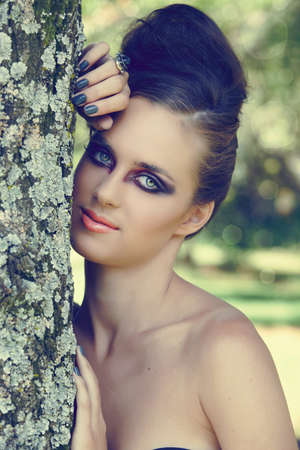 beautiful woman with dramatic eye make-up, gray manicure & beehive hairstyle outdoors next to the tree with natural bokeh effect, split tone colour for fashion look. Stock Photo - 9156670