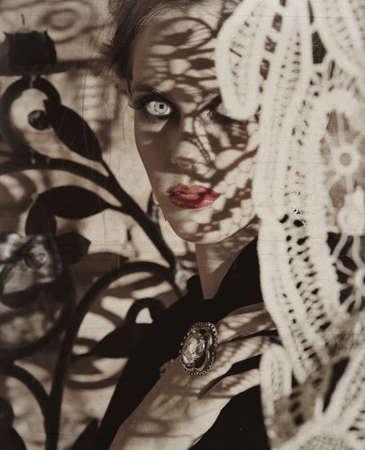 belle jeune femme avec des lèvres rouges regarde derrière les rideaux de dentelle antique avec les ombres de la dentelle sur son visage grunge griffé arrière-plan Banque d'images