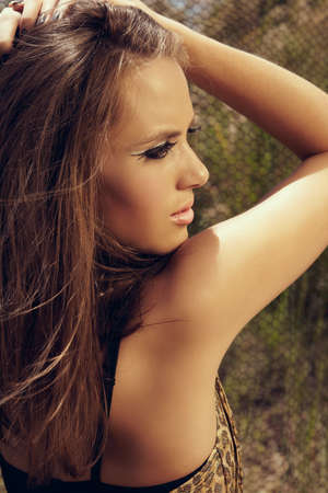 beautiful young woman with long brown hair wearing leopard print dress and cat eye fashion make-up with false lashes, shot outdoors in the middle of the day for saturated summer look. photo