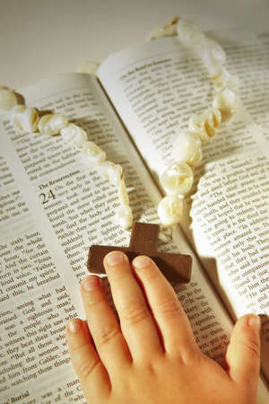 small childs hand touching wooden cross on pearl rosary on an open Bible with text of Resurrection in warm afternoon sun. photo