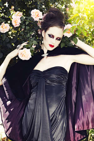 beautiful woman wearing silk dress and velvet cape against very pale white skin Stock Photo - 9156539