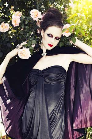 velvet dress: beautiful woman wearing silk dress and velvet cape against very pale white skin