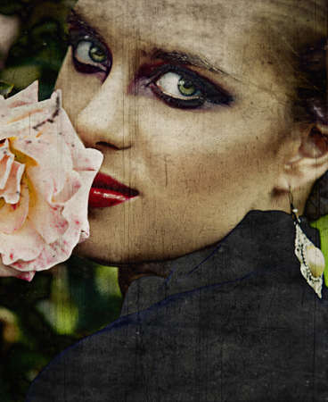 beautiful young woman with artistic fashion make-up smelling a pink rose in the garden in vintage finish with scratches. photo