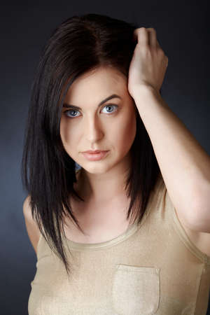 raised eyebrow: beautiful young woman with blue eyes and dark hair in structured bob haircut touching her hair with curious expression Stock Photo