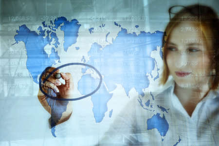 stock predictions: young business woman doing stock market analysis and marking the crisis area on the world map .
