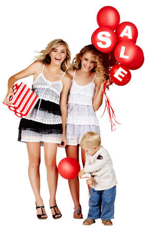 two beautiful girls laughing with red balloons with sign sale and gift box and little boy playing next to them. photo
