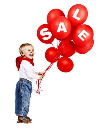 mignon petit garçon en chemise blanche, jean et foulard rouge rire comme il tient un bouquet de ballons rouges avec le signe de la vente
