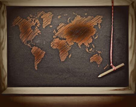 map pencil: grunge orange world map sketch on a  retro blackboard with a pencil. Stock Photo