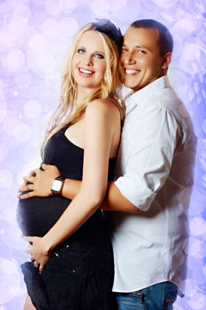happy embracing couple on purple background with pregnant mother wearing black dress and husband white shirt. photo