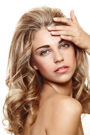 belle jeune femme aux cheveux frisé longtemps blond toucher sa peau sur fond blanc.