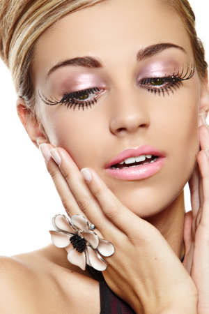 beautiful blond woman with long false eyelashes and pink eyeshadow and lipstick wearing large cocktail flower ring with a surprised expression.
