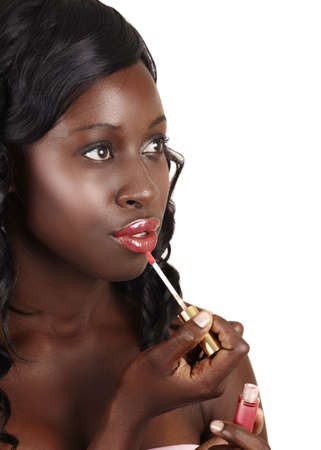 beautiful African American young woman with long curly hair applying red lip gloss to her full lips - easy to extend background for copy space over white. photo