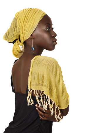 beautiful South African young woman with head wrapped in traditional style yellow scarf looking seriously in profile.