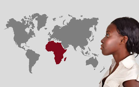 young African American woman thinking and looking at the world map with Africa in red. Foto de archivo