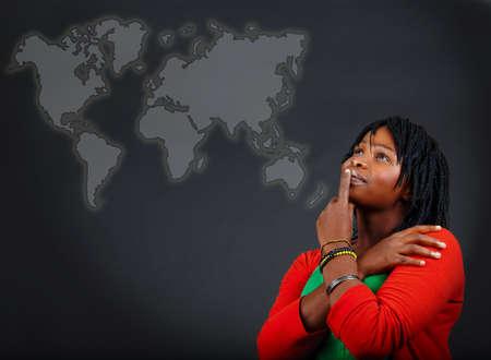 negocios internacionales: joven mujer afroamericana pensando y mirar el mapa del mundo con una actitud positiva.