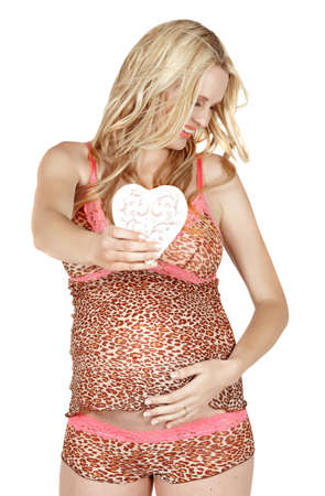 beautiful smiling pregnant woman holding heart and wearing lingerie on white studio background. photo