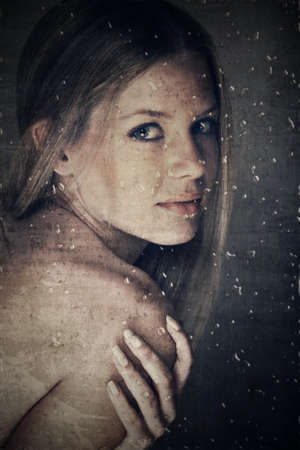 beautiful woman with natural make-up and long hair behind glass with raindrops on grunge texture photo