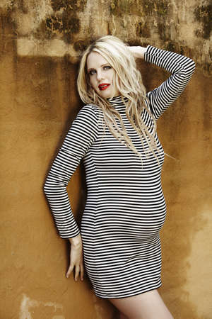 Beautiful eight months pregnant blond woman with curly hair in a black and white stripes fashion mini dress against a grunge wall background . photo