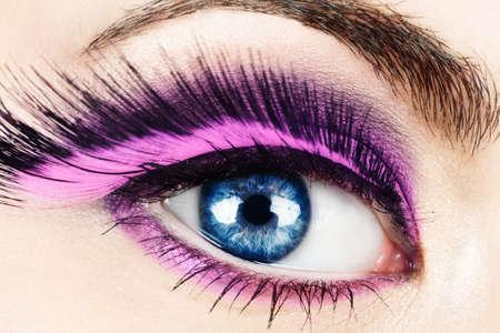 fake: Macro of womans eye with long pink feather fake eyelashes.