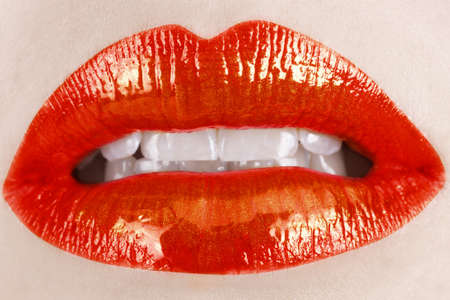 macro of woman's lips with bright red lipstick on full lips