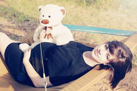Beautiful eight months pregnant brunette woman wearing a black dress lying on the hammock with a toy bear in the park - bear modified from original . Stock Photo