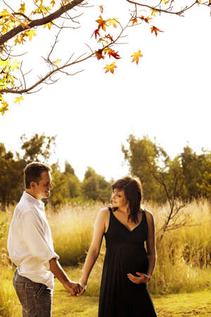 happy young pregnant woman in long black dress and her husband outdoors in autumn field holding hands. photo