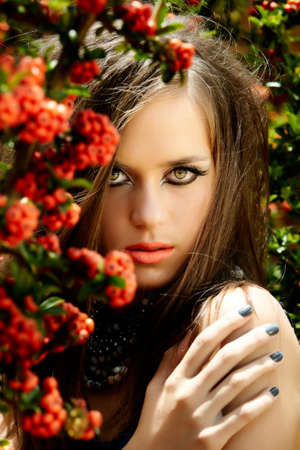 beautiful young woman with long brown hair and green eyes wearing artistic makeup and coral lipstick standing in the summer day in red berries. photo