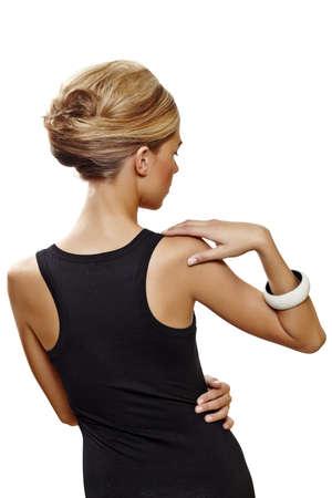 Cheveux chaussés de belle femme en français updo de rouleau en robe noire sexy permanent avec son dos sur fond blanc. Banque d'images - 10012631