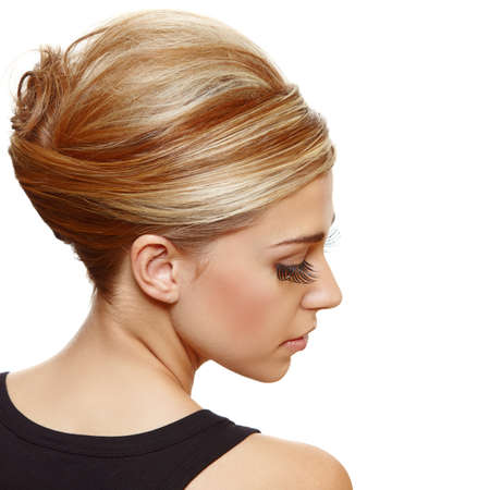 beautiful blond woman with false long eyelashes wearing hair in a classic french roll updo style. photo