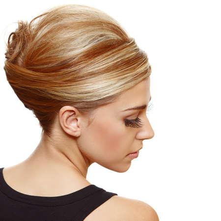 belle femme blonde avec fausses cils longs portant des cheveux dans un style updo de rouleau français classique.