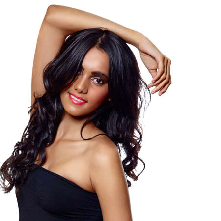 beautiful woman with long black curly hair, tanned skin and natural make-up over white background. photo