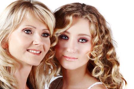 hermosa madre e hija con maquillaje y cabello largo Rubio felices juntos sobre un fondo blanco studio