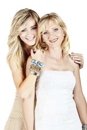 vacker mor och dotter med make-up och långa blonda hår lyckliga tillsammans på en vit studio bakgrund Stockfoto