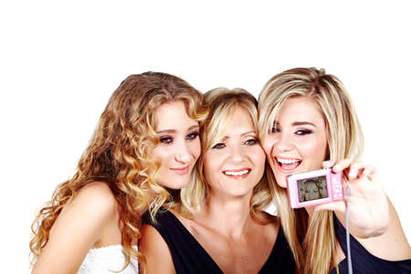 three women: beautiful mother and daughters with make-up and long blond hair happy together on a white studio background taking picture with digital camera Stock Photo