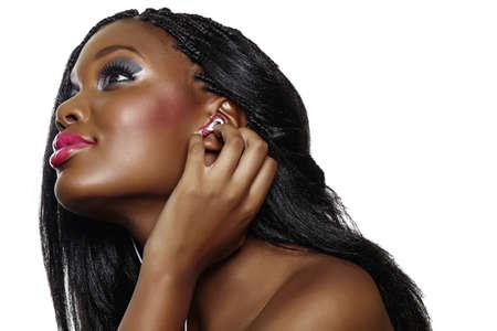hairdo: Si felice sudafricano donna con il trucco bello ascoltare musica su auricolari su sfondo bianco.
