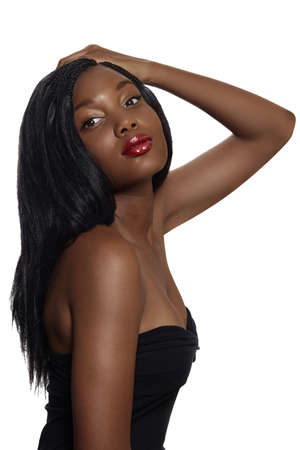mujeres negras: Retrato de joven sudafricana hermosa con el pelo suelto de pelo largo y labios rojos brillantes con corsé negro sobre fondo blanco.