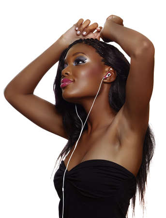 You happy South African woman with beautiful makeup listening to music on earphones over white background and dancing photo