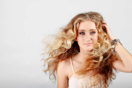 Belle jeune fille blonde adolescente de fraise avec des yeux verts et de longs cheveux bouclés soufflant dans le vent sur fond de studio gris avec copie espace Banque d'images - 10012597