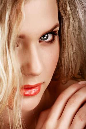 Närbild porträtt av ung vacker blond kvinna med långt lockigt hår och naturligt fräsch make-up och sommar solbränna