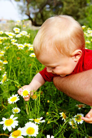 little boy and his father enjoying outdoors in field of flowers photo